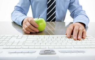 man with apple at computer
